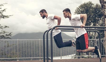 Two sportsmen doing dips on parallel bars