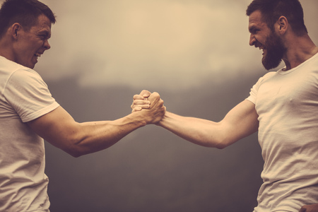 Deux athlètes caucasiens en tenue sportive mesurant les forces lors d'un entraînement en plein air Banque d'images