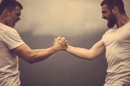 Zwei kaukasische Sportler in Sportkleidung messen Kräfte beim Outdoor-Training Standard-Bild