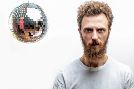 Portrait of a serious man holding a disco ball - mirror ball in hands Stock Photo