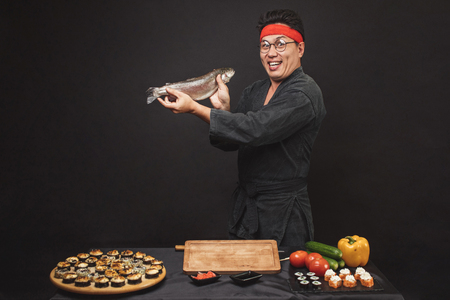 excited chef with fish isolated black background