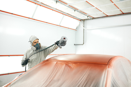 auto painter in protective workwear and respirator painting car body in paint chamber