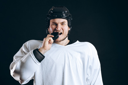 Hockey player bites the puck with broken teeth and looking at camera with a grin. Stock Photo
