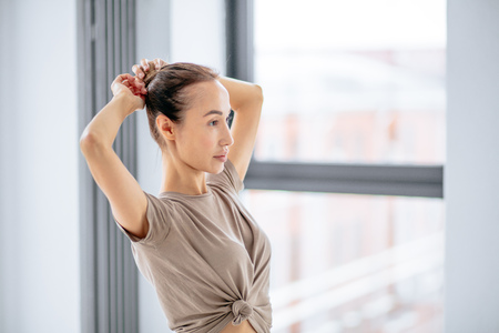young awesome woman ddoing a hairbun before yoga classes