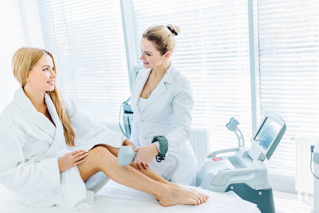 Blonde woman on hair removal cosmetology procedure. Laser epilation concept.