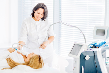 Face skin care. Woman getting facial laser treatment Stock Photo