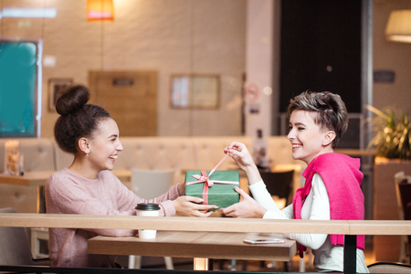 Happy woman congratulates her girlfriend with present box while sitting at cafe. Banco de Imagens