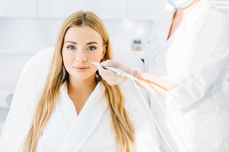 Blonde woman undergoes a procedure of facial gas-liquid oxygen peeling Stock Photo