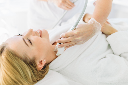 Blonde woman with long hair makes face laser resurfacing At Beauty Center
