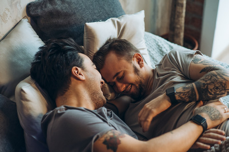 A homosexual couple on bed in studio with loft interior