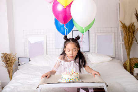 little Asian girl blowing out candles on cake and making a wish.