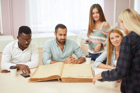Diverse multiracial students spending leisure time in library with big old book