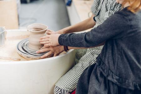elder sister teachs little sister to make a pottery
