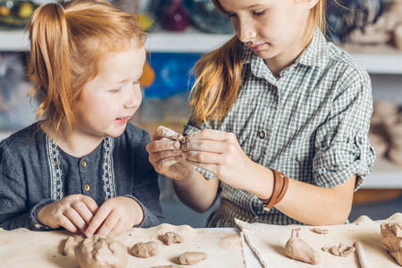 girl showing her little sister to create a clay toys