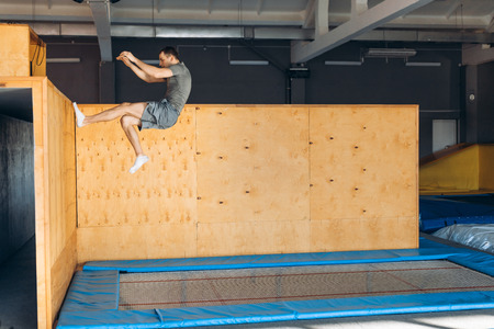 young active man doing stunts with wall