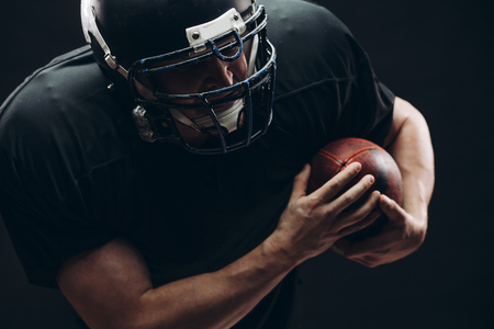 American football player with helmet and armour with a ball against black wall