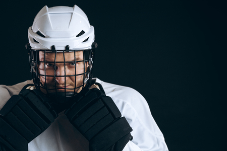 Portrait of ice-hockey player with hockey stick and protective gloves