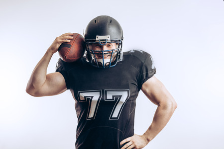 Muscular american football player in protective uniform and helmet holding ball Standard-Bild