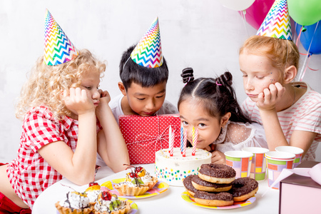 attractive nice asian girl smelling the cake while sitting among her friends Foto de archivo