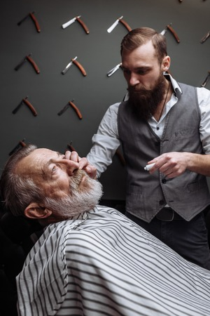 Old man getting his beard shaved by barber Foto de archivo