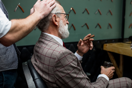 Bearded old businessman sitting at barber shop in chair choosing haircut design
