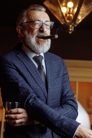 Elderly businessman in formal suit with whiskey and cigar at lux Imagens