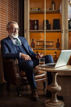 Senior dramatist looking at laptop, creating novel while sitting