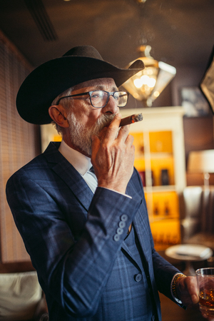 Portrait of old-aged male dandy in big hat smokes cigar and drinks alcohol.