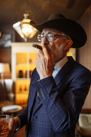 Concept of old age wisdom and experience. Old man with cigar and whiskey.