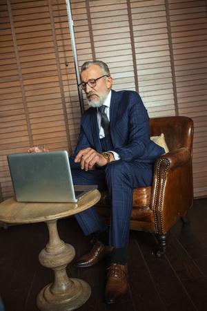 Senior dramatist looking at laptop, creating novel while sitting in pub. Foto de archivo