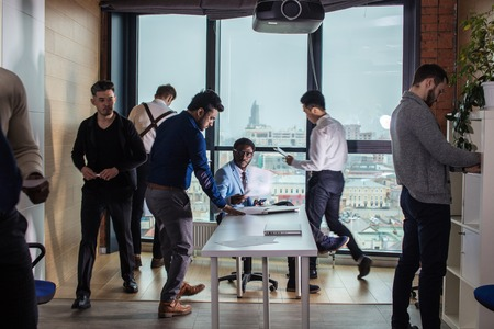 Business people in an open space office with a panoramic window, long shot Stock Photo