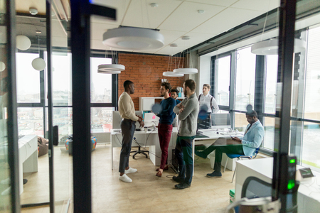 Business people in an open space office with a panoramic window, long shot 스톡 콘텐츠
