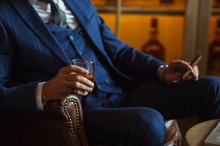 Elderly businessman with glass of whiskey and cigar on dark background Banque d'images