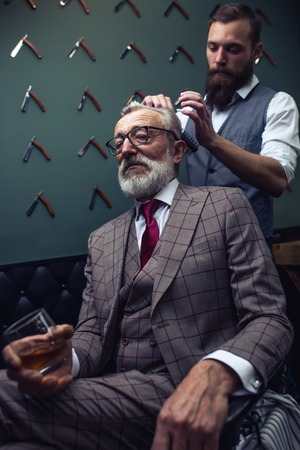 Senior man visiting hairstylist in barber shop. Foto de archivo