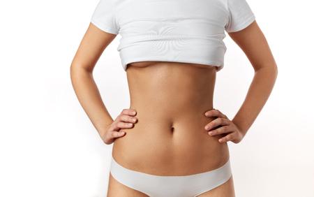 Corazón de concepto de embarazo de mujer embarazada en el estómago. Manos formando corazón en el ombligo femenino. Concepto de salud de estómago saludable o concepto de embarazo temprano con hermosas manos femeninas. Modelo de mujer. Foto de archivo