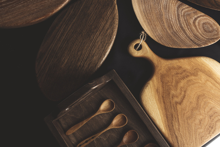 A variety of handmade DIY wooden kitchenware bowls, chopping boards, wooden trays from valuable timber on black background 免版税图像