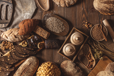 Whole grain, whole loaf and sliced pieces of multigrain bread contains whole grains ( poppy, millet, flaxseed, pumpkin seeds, and sunflower seeds) isolated on dark wooden table . 免版税图像
