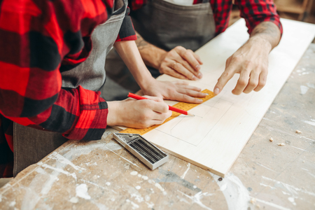 profession, carpentry, woodwork and family concept - carpentery masterclass for little children and their fathers to share basic knowledge of working with wood.