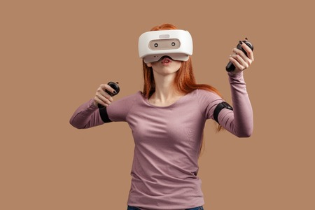 Casual ginger-haired woman in purple pullower wearing VR headset and looking involved in 3D simulation game, gesturing hands as if he interacting with somebody, isolated over beige background