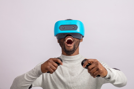 African happy overjoyed guy in VR glasses driving virtual car isolated over white background learning to drive a car. Virtual driving school or studio concept