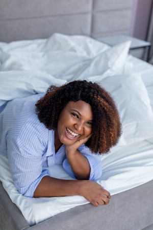 laughing woman posing to the camera while lying under the blanket. close up photo. fun, happiness, emotion, feeling Stock fotó
