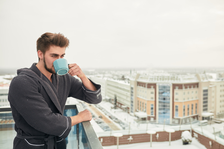 Healthy bearded caucasian man drinking hot tea, looking at winter cold frosty city, standing on outdoor terrace in bathrobe. Bracing morning, fresh mind