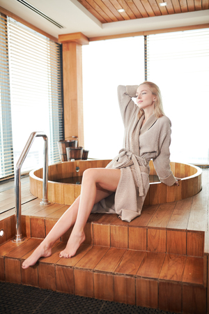 attractive blonde caucasian woman in bathrobe relaxing near wooden barrel bath in spa, enjoying still life of a steam bath room.