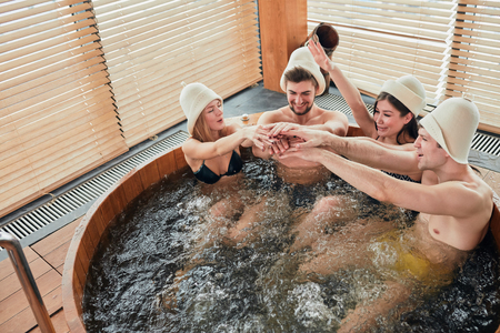 Group of male and female friends visiting bathhouse in holidays, being overjoyed and happy, enjoying jacuzzi in hot wooden round barrel Фото со стока
