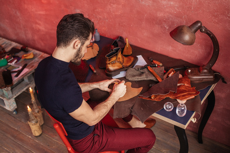 special method of making shoes. top angle view .man taking part in a shoe design course