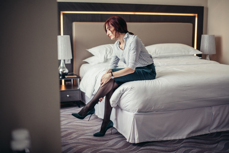 Elegant red-haired lady touching with arms her legs, being tired from wearing stilettos while sitting in bedroom after returning home from office.