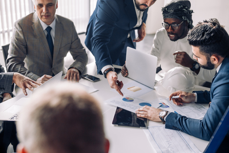 Multiracial group of male experts analyzing business resuls , close up of team with smartphones and tablet pc sitting at table in office, actively speaking, engaging with each other and working