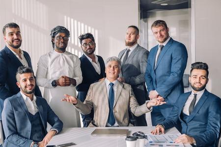 Interracial Management eines großen internationalen Unternehmens anlässlich des 50-jährigen Firmenjubiläums mit dem reifen grauhaarigen CEO in der Mitte