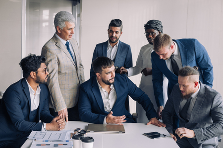 Confident team of age and race diverse male professionals dressed in formal wear excited with success of construction company gatther around boss tabledesk.