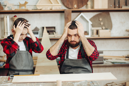 Portrait of shocked carpenter man and his son in red checkered working shirts, keeps hands on head, looking as if they did a mistake and do not know what to do. Family relations and Human emotions